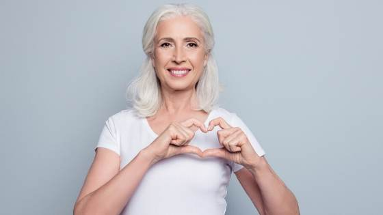 Woman making a heart with her hands for American Heart Month